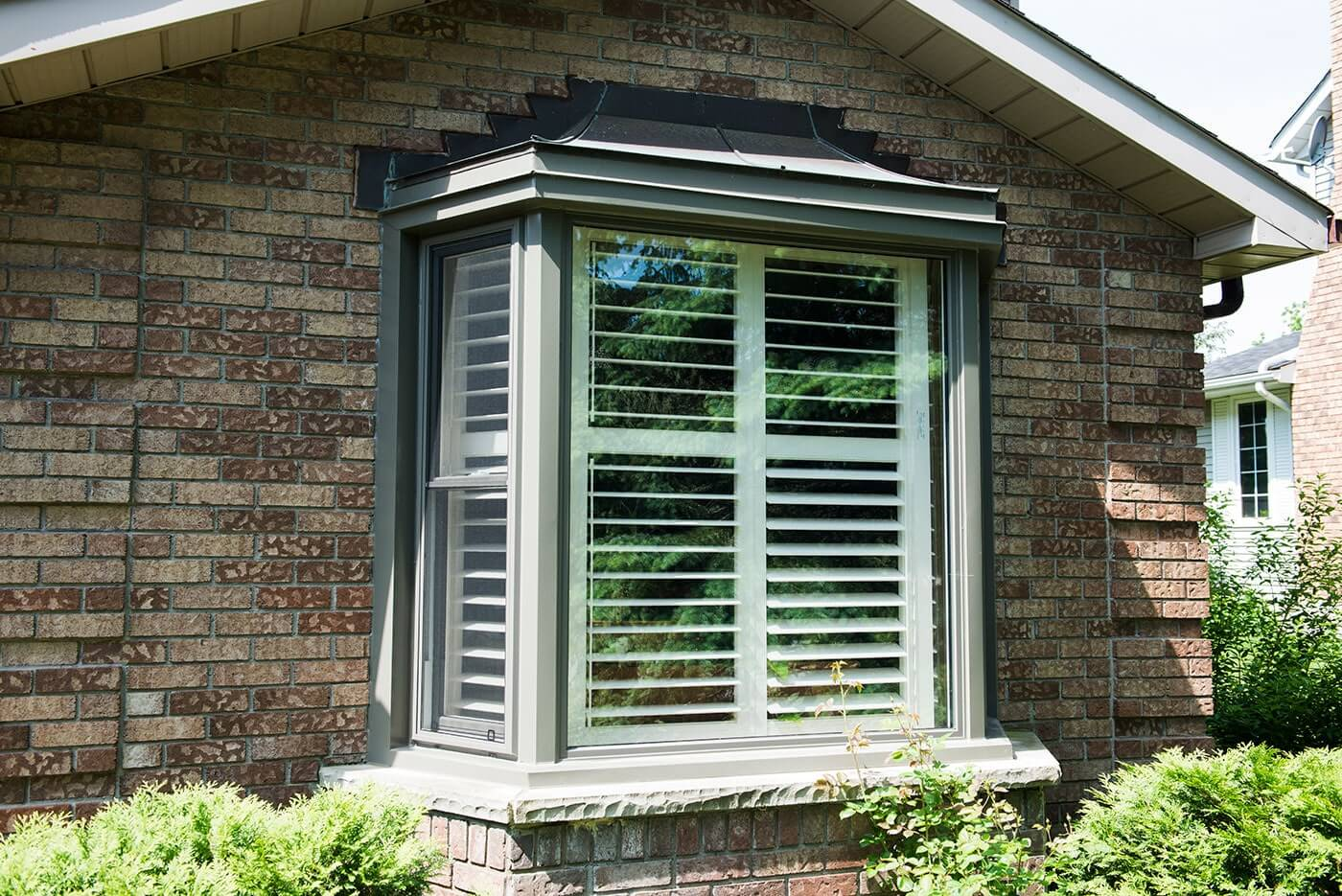 Custom Made Bay Window With Dark Grey Trim On The Side of Brick Home