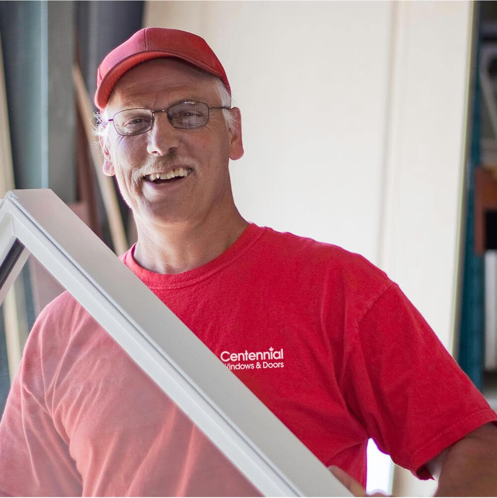 Centennial Windows and Doors Employee Smiling as He Installs Custom Window