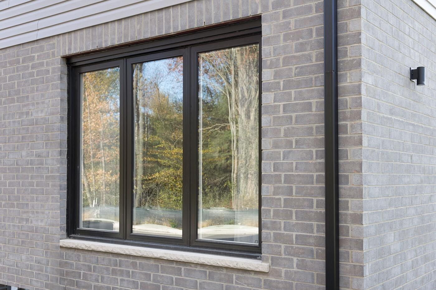Custom Made Triple Fixed Picture Window on Home With Grey Bricks