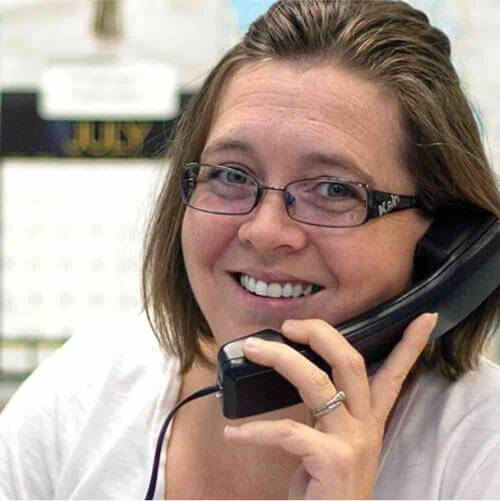 Female Customer Service Representative On The Phone And Smiling At Camera